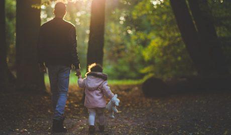 un père et sa petite fille en balade dans une forêt