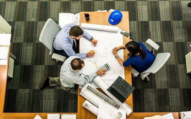 trois personnes autour d'un bureau